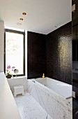 Bathtub with marble surround against wall with dark mosaic tiles in modern bathroom