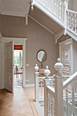 Open-plan staircase with carved balustrade in renovated house