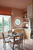 Rococo-style chairs around set breakfast table in rustic kitchen