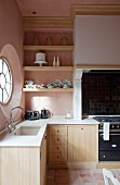 Simple kitchen with wooden base units and pink walls