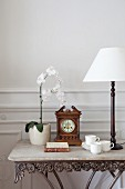 Orchid, antique table clock and table lamp with white lampshade on antique console table with stone top
