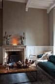 Couchtisch und antikes, gepolstertes Sofa um Kamin, auf Steinsims Engelfiguren als Kerzenhalter, in renoviertem Kaminzimmer