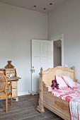 Geschnitztes Kinderbett mit hohem Kopfteil in renoviertem Kinderzimmer