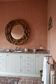 Detail of washstand with wooden front painted pale grey below round mirror with wooden frame on pink-glazed wall