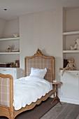 Antikes Schlittenbett mit geschnitzem Holzrahmen, weisse Bettwäsche, zwischen Nischen mit eingebauten Regalböden und Unterschrank