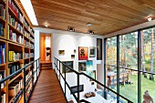Bookcase on airy steel and wood gallery opposite glass wall with gallery of paintings on end wall