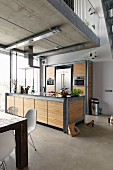 Modern kitchen area below gallery; counter and cupboards made from galvanised steel and zebrano veneer