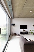 Contemporary living room with glass wall, exposed concrete ceiling, standard lamps with black lampshade and flatscreen TV on wall
