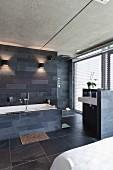 Designer bathroom area with slate tiles on walls and floor in open-plan bedroom