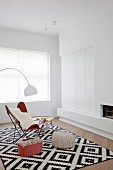 Butterfly Chair und Strick-Pouf auf grafisch gemustertem schwarz weißem Teppich