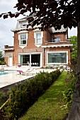 Pool mit Sonnenterrassen vor traditionellem, belgischem Backsteinhaus mit weissen Zierelementen und modernen, grosszügigen Fenstern