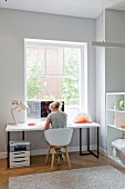 Bright, modern study with woman sitting on shell chair at desk below window