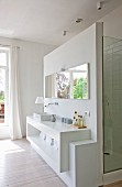 Cubic washstand with shelf and mirror on wall screening shower cubicle in open-plan ensuite bathroom