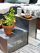 Potted herbs and pastries on set of rusty metal and mesh side tables