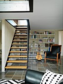 Metal staircase with wooden treads in living room with black leather armchair in front of modern shelving in background