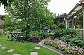 Gartenplatz mit Holztisch und -stühlen, seitlich angelegte Beete mit blühenden Blumen vor Anbau