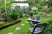 View past weathered wooden table and chair to greenhouse and flowerbeds in summer garden