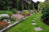 Blühende Blumen im Beet mit Steineinfassung und Trittplatten in gemähter Rasenfläche im Garten