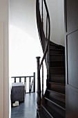 Winding wooden staircase painted a dark shade