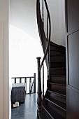 Blick auf gewendelte, dunkel lackierte Holztreppe