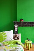 Bed in front of mantelpiece of disused fireplace in child's bedroom with green wall