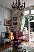 Stühle im Rokoko Stil neben Kommode in Zimmerecke, Vordergrund Kronleuchter mit Kristallschmuck