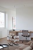 Maßgefertigter moderner Holzschreibtisch mit Klassiker Bürostuhl im gemütlichen Loungebereich mit Eames-Schaukelstuhl und Tierfell
