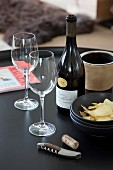 Bottle of fine wine, two wine glasses, bowl of crisps and corkscrew on black tray table