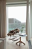 Leseecke mit Eames-Schaukelstuhl, Tierfell und rundem Tisch mit Büchern vor raumhoher Verglasung und beigefarbenen Vorhängen