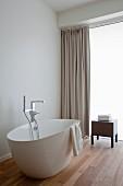 Freistehende weiße Badewanne auf Teakholzparkett, dahinter bodenlanger beigefarbener Vorhang, Hocker und satinierte Verglasung