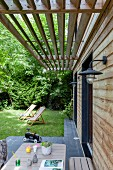View over table on terrace to deckchairs in garden outside house with wooden slatted sunshade
