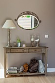 Table lamp with white lampshade and candle lanterns on rustic wooden console table below oval mirror on wall painted pale grey