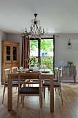 Pale wooden chairs and table in front of rustic corner cabinet next to French windows