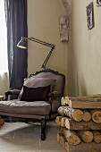 Rococo-style armchair and standard lamp in corner next to stack of firewood against wall