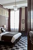 Blick durch offene Tür auf Doppelbett und Schachbrettmusterboden in elegantem Schlafzimmer