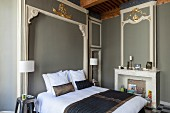Double bed in bedroom with Baroque elements: stucco elements, some gilded, on grey-painted walls