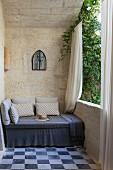 Gemütliche Sitzbank mit grauer Husse und Kissen auf Balkon mit Natursteinwänden
