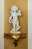 Cherub on gilt bracket on gold stripe on wall