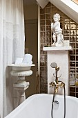 Bathtub with vintage-style tap fittings and white cherub on masonry shelf in renovated interior