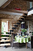 Table with green tablecloth and wicker chairs at foot of window staircase in interior with stone walls