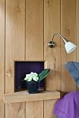 Holzverschalte Wand und Blumentopf auf Konsole vor kleiner Nische, seitlich Wandleuchte
