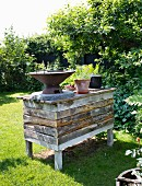 Barbecue and potted plants on counter made from reclaimed boards in sunny garden