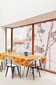 Retro chairs around table with orange tablecloth next to windows with roller blinds
