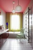 Modernes farbenfrohes Badezimmer mit pinker Decke, gelbem gelochtem Vorhang, mintgrünem Stuhl und blauer Glasvase