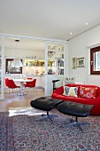 Glasschiebetür zwischen Essbereich und Wohnraum, rote Designercouch mit schwarzen Lederhockern