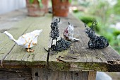 Various animal and bird figurines on weathered wooden table