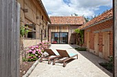 Sun loungers and pink hydrangeas in paved courtyard of renovated farmhouse