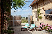 Sonnenliegen und blühende Hortensien in gepflastertem Innenhof eines renovierten Bauernhofes