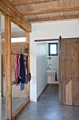 Timber-framed cloakroom area with view into toilet through rustic vintage sliding door