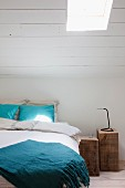 Zwei rustikale Holzblöcke als Nachttische neben Bett und weiß gestrichene Dachschräge mit Dachflächenfenster
